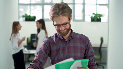 Bearded emotional manager checks information looking in papers standing in the Footage