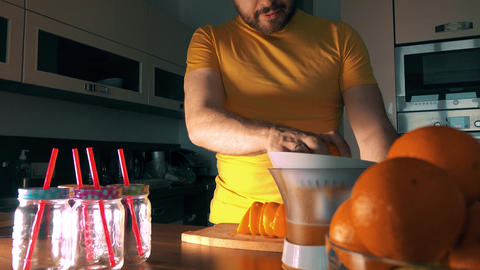 Man squeezing fresh orange juice with a juicer Footage