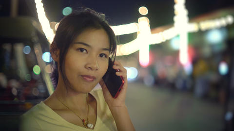 Happy Asian woman talking on phone in night city Footage
