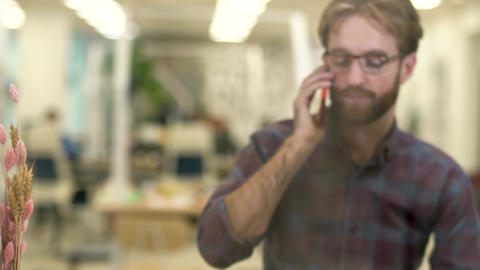 Bearded smiling guy with glasses and casual plaid shirt talking on a cell phone ビデオ