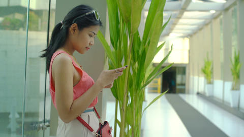 Young Asian woman with smart phone near window Footage