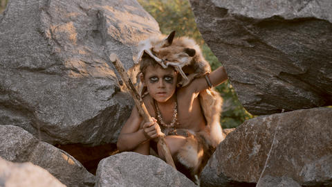Caveman, manly boy hunting outdoors. Ancient warrior portrait Live Action