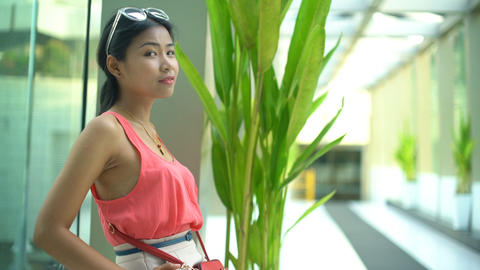 Pretty Asian girl is standing near window in the office Footage
