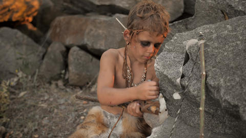 Caveman, manly boy making primitive stone weapon in camp ビデオ