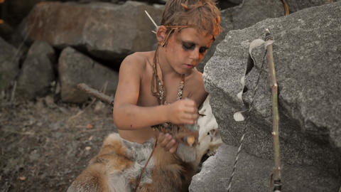 Caveman, manly boy making primitive stone weapon in camp Stock Video Footage