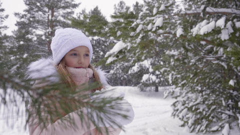Girl blow snow from palms throw snow up and turn around in forest winter Live Action