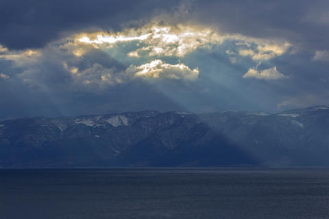 A mystical landscape. The sunset rays that descend over Mountain hills and Lake フォト