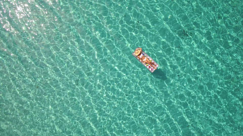 Aerial - Beautiful woman floating on inflatable mattress in crystal clear water Footage