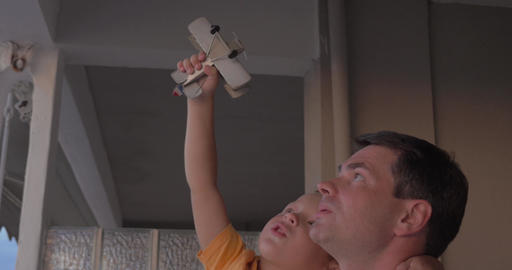 Father and child playing with toy plane Footage