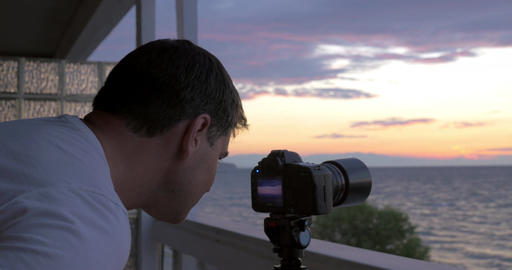 Man shooting timelapse of sunset over the sea Footage