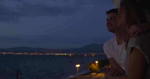 Couple looking at sea from hotel balcony at night Footage