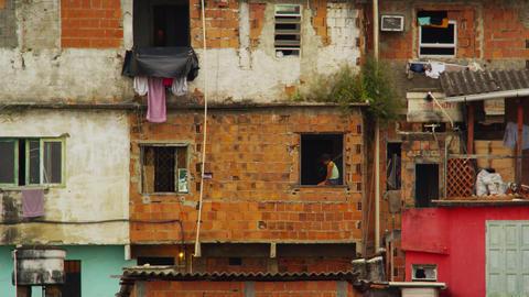 RIO DE JANEIRO, BRAZIL - JUNE 23: Slowmo of child in window sill in favela of Ri Footage