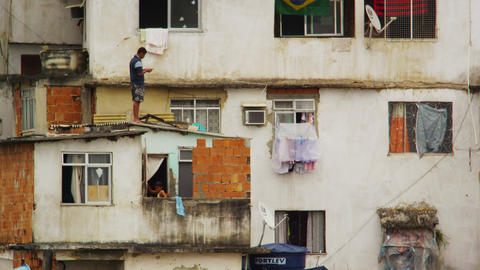 RIO DE JANEIRO, BRAZIL - JUNE 23: Man on a rooftop and girl in window in Rio de  Footage