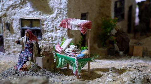 Largest animated nativity scene in South America. Woman sews clothes Live Action