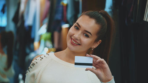Young girl in shop with shopping and credit card Footage