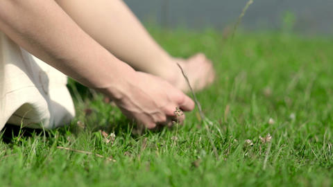A girl sits on the green grass by the river Footage
