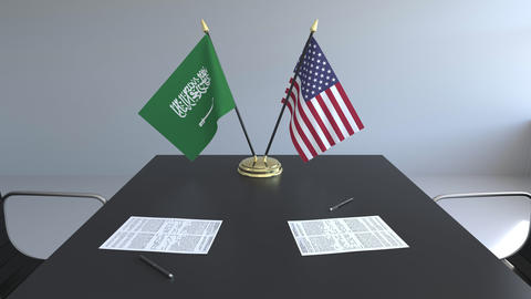 Flags of Saudi Arabia and the United States of America and papers on the table Live Action
