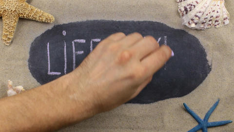 Word LIFESTYLE, written on a chalkboard among seashells and starfishes lying on Footage