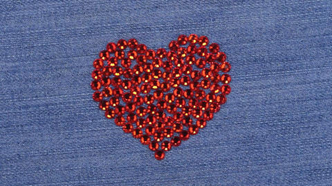 Rotation. Symbolic red heart made of rhinestones, a symbol of love. View from Live Action