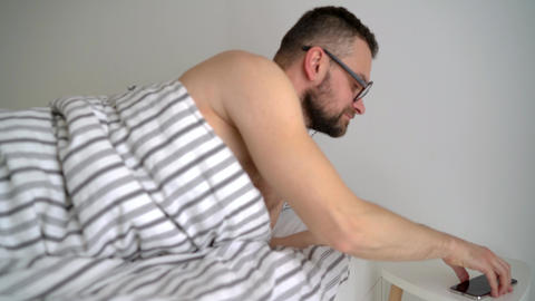 Bearded man waking up in bed under blanket, smiling,... Stock Video Footage
