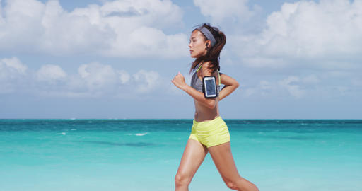 Determined Runner Listening Music While Jogging At Beach During Sunny Day Live Action