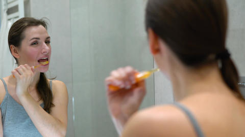 Pretty woman brushing her teeth in a bathroom in the morning. Morning hygiene Live Action
