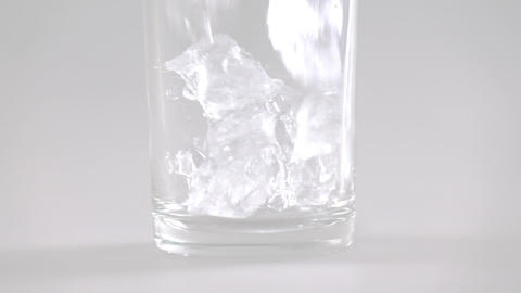 Close up of ice cubes falling into glass slow motion GIF
