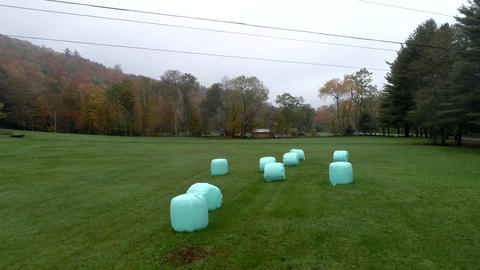 Aerial Drone - Fly Low Over Plastic Wrapped Bales of Hay in Fall in Vermont Footage
