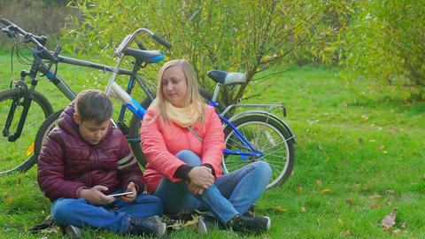 boy sitting on the grass and playing smartphone. Mom takes her son's smartphone Live Action