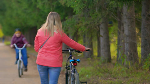 Woman walking with a Bicycle in the Park. She's walking away from the camera Live Action