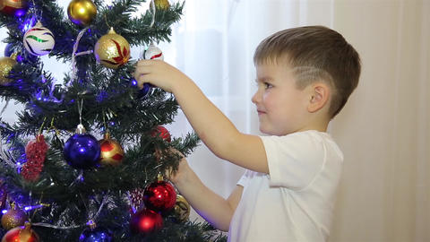 A small child looks at the Christmas tree toys HD Footage