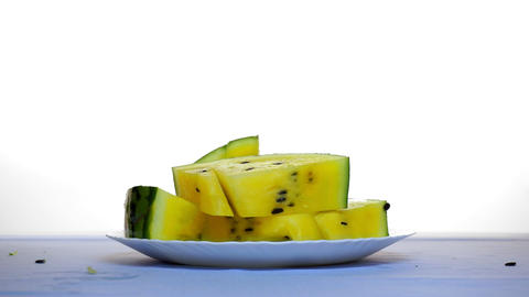 On the table slices of yellow watermelon. Another slice falls from above Footage