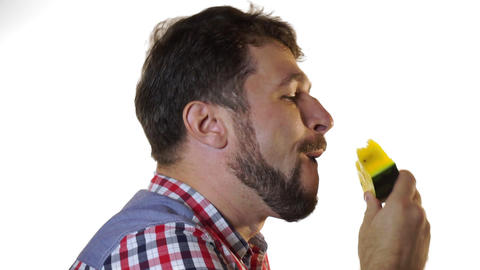 A bearded man bites a slice of juicy yellow watermelon Footage