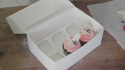 Woman is packing cupcakes in a box Live Action