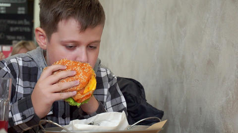 A teenager in a cafe eating a hamburger. He is hungry, tasty and juicy hamburger Live Action
