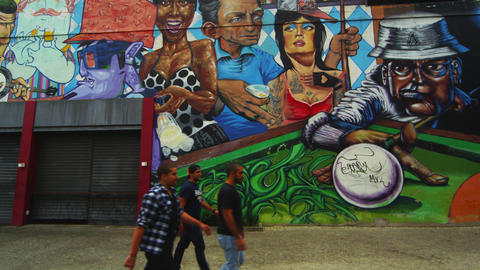 RIO DE JANEIRO-JUNE 23: Three men walk past a wall colorful with art on June 23, Footage