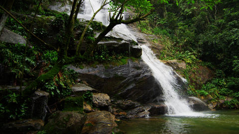 Tracking shot of a jungle waterfall cascading down into a dark green pool Footage