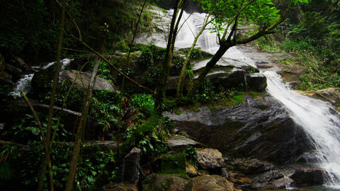 Tracking shot of a jungle waterfall rushing down a rocky hillside into a deep gr Footage