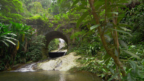 Tracking shot of a jungle stream and waterfall as seen through a stone bridge Footage