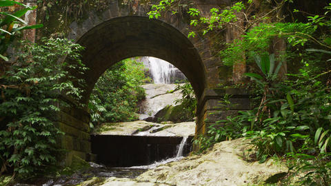 Tracking footage of a scenic jungle stream flowing underneath an arched bridge Footage