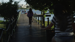 Women biking onto small lake pier Footage