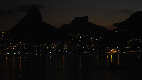 Night rower silhouetted against illuminated Rio Footage