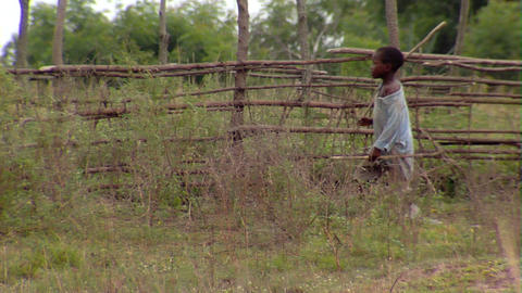 African boy walking outside of his hut Footage