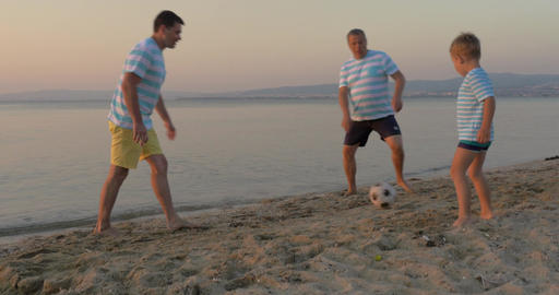 Men of three generations playing football on beach Footage