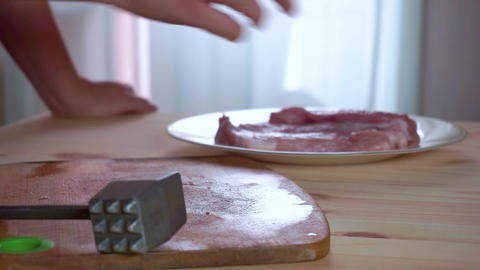 Housewife puts a piece of fresh pork and beats it Footage