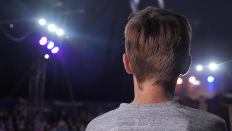 Back view: excited male child watching acrobatic performance on the stage Footage