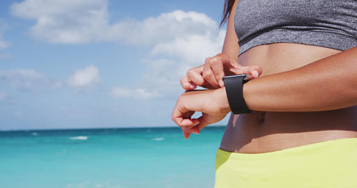 Smartwatch - Female Runner Using Smartwatch During Exercise At Beach In Summer Live Action