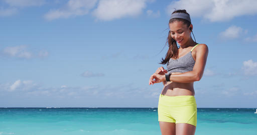Smiling Young Jogger Using Smartwatch While Exercising At Beach Live Action