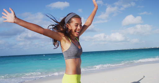 Cheerful Woman In Sportswear Cheering While Running At Beach Against Sky Live Action