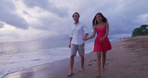 Honeymoon passionate couple holding hands walking on beach Live Action